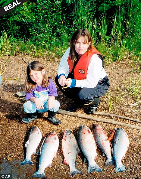 Sarah Palin posing with one of her daughters - and some fresh-caught salmon